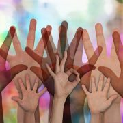 many hands raised on colorful background