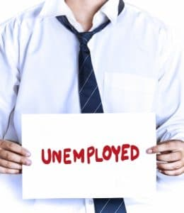"Man holding sign reading ""unemployed."""